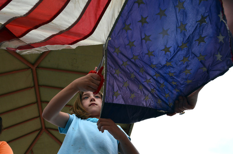 Avery Foglesong, 6, cuts the field of stars from the strips of a flag for retirement during Thursday's 8th Annual Flag Retirement Ceremony at the Community Park Amphitheater.<br /> <br /> June 14, 2012 <br /> staff photo/ David R. Jennings