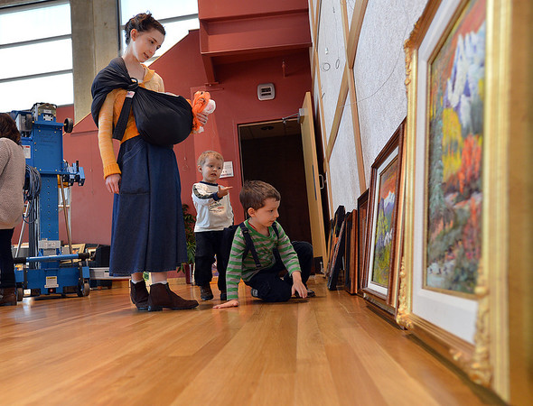 Broomfield Art Guild member Andrea England with her son's Tobias, 6, David, 3, and holding, Samson, 8 weeks-old,  looks at some of the  38 art pieces from 25 artists in the lobby of the Audi on Friday.<br /> November 16, 2012<br /> staff photo/ David R. Jennings
