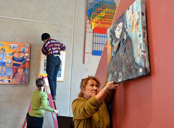 Roxanne Macke, right, with the Broomfield Art Guild, hangs a painting with help from the Audi staff members Kitty Angell and Stephanie Dallmann as they hang 38 art pieces from 25 artists in the lobby of the Audi on Friday.<br /> November 16, 2012<br /> staff photo/ David R. Jennings