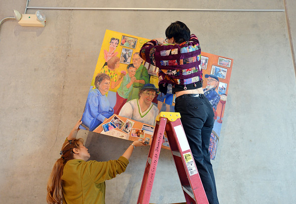 Artist Roxanne Macke, left, and Kitty Angell, Broomfield Audi staff, work on hanging  38 art pieces from 25 Broomfield Art Guild artists in the lobby of the Audi on Friday.<br /> November 16, 2012<br /> staff photo/ David R. Jennings