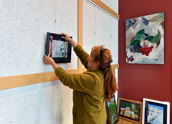 Broomfield Art Guild member Roxanne Macke figures out where to hang the 38 art pieces from 25 artists in the lobby of the Audi on Friday.<br /> November 16, 2012<br /> staff photo/ David R. Jennings