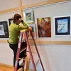 Stephanie Dallmann, Broomfield Audi staff, checks the level of a painting while helping hang  38 art pieces from 25 Broomfield Art Guild artists in the lobby of the Audi on Friday.<br /> November 16, 2012<br /> staff photo/ David R. Jennings