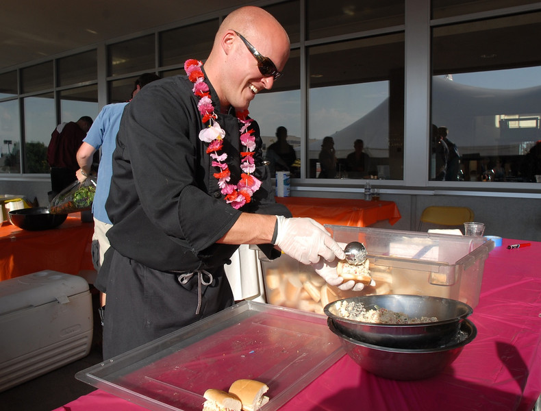 Flatz Restaurant chef Sean Rush prepares sandwiches for participants at the Broomfield Community Foundation's 2009 Broomfield BASH at the Beach fundraiser held at Sill-TerHar Motors on Saturday.<br /> <br /> July 18, 2009<br /> staff photo/David Jennings