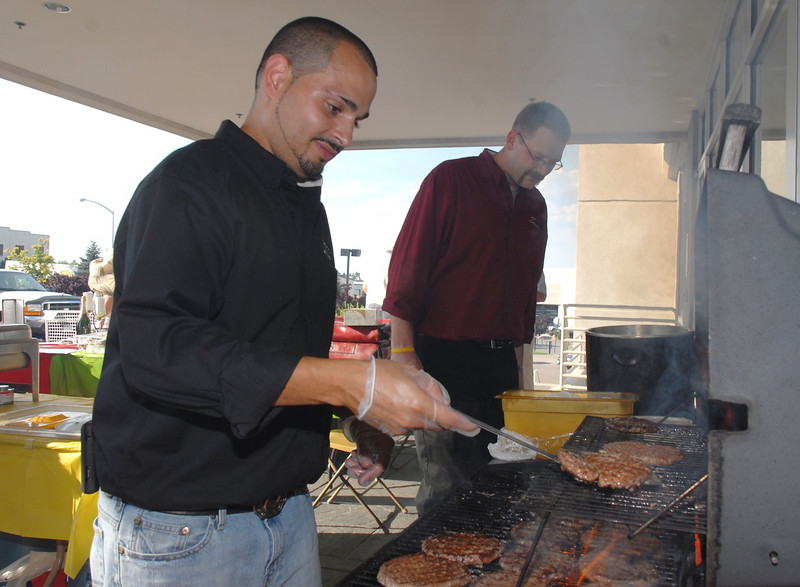 Manny Quintero cooks hamburgers for the Fox and Hound Restaurant during the Broomfield Community Foundation's 2009 Broomfield BASH at the Beach fundraiser held at Sill-TerHar Motors on Saturday.<br /> <br /> July 18, 2009<br /> staff photo/David Jennings