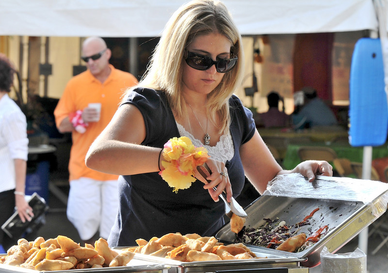 Rachel Campbell prepares food at the Gordon Biersch Brewery Restaurant booth  during the Broomfield Community Foundation's 2009 Broomfield BASH at the Beach fundraiser held at Sill-TerHar Motors on Saturday.<br /> <br /> July 18, 2009<br /> staff photo/David Jennings