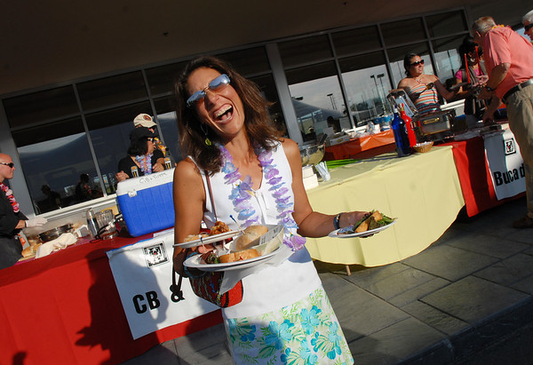 Tamra Obenauer  takes plates of food to her friends during the Broomfield Community Foundation's 2009 Broomfield BASH at the Beach fundraiser held at Sill-TerHar Motors on Saturday.<br /> <br /> July 18, 2009<br /> staff photo/David Jennings