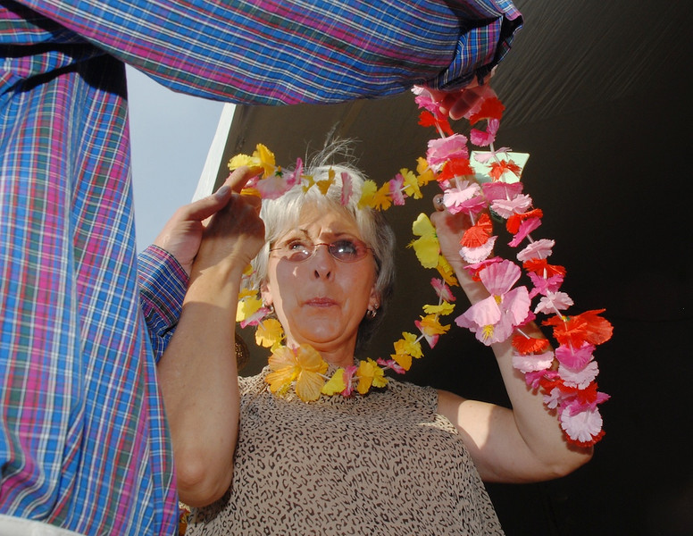 Gail Eberhart puts on a Hawaiian lei with her husband Dan's help during the Broomfield Community Foundation's 2009 Broomfield BASH at the Beach fundraiser held at Sill-TerHar Motors on Saturday.<br /> <br /> July 18, 2009<br /> staff photo/David Jennings