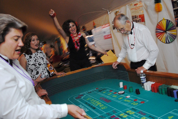 Lisandra Gonzalas, center, cheers after rolling the dice during the Broomfield Community Foundation's 2009 Broomfield BASH at the Beach fundraiser held at Sill-TerHar Motors on Saturday.<br /> <br /> July 18, 2009<br /> staff photo/David Jennings