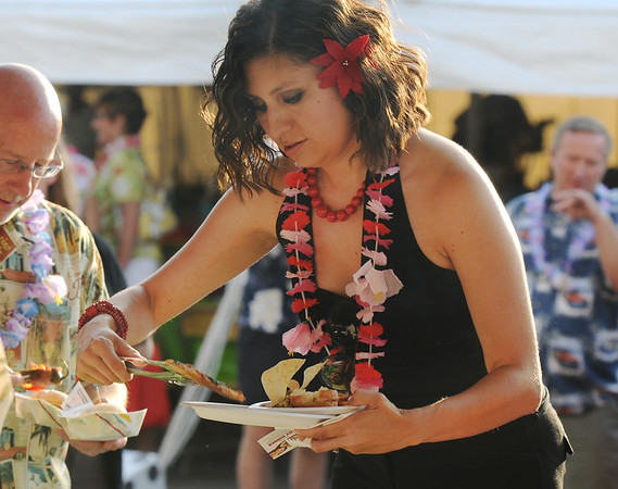 Lisandra Gonzalas with CASA, samples food from the 15 restaurants at the Broomfield Community Foundation's 2009 Broomfield BASH at the Beach fundraiser held at Sill-TerHar Motors on Saturday.<br /> <br /> July 18, 2009<br /> staff photo/David Jennings