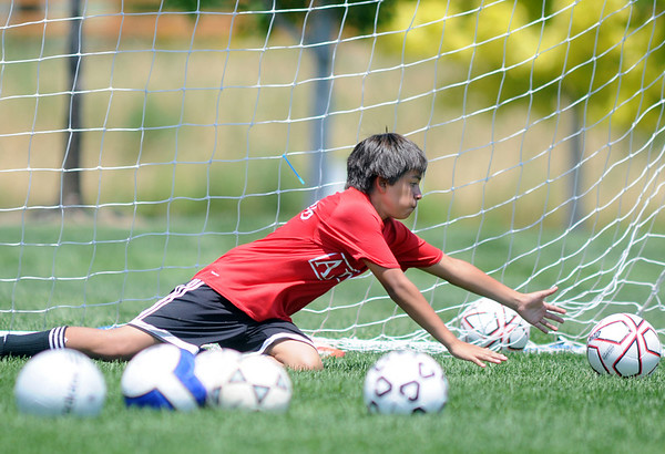 Isaiah Mondragon, 12, reaches to keep the ball from the gaol during keeper training at the Broomfield Blast technical touch camp at the Broomfield County Commons Park on Wednesday.<br /> <br /> July 22,2009<br /> staff photo/David Jennings