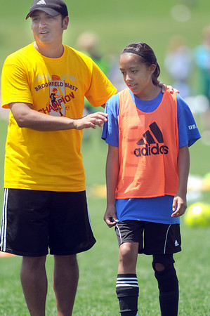 Legacy High soccer coach Chris Trujillo, left, uses Ariana Jimenez, 13, to walk through a problem play  during the Broomfield Blast technical touch camp at the Broomfield County Commons Park on Wednesday.<br /> <br /> July 22,2009<br /> staff photo/David Jennings