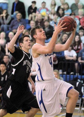 Aric Kaiser, Broomfield goes to the basket past Connor Skelton, D'Evelyn during Friday's 2nd round of the state 4A boys playoffs at Broomfield.<br /> February 25, 2011<br /> staff photo/David R. Jennings