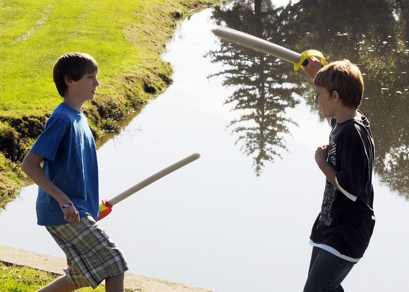 Sam Burnell, 13, left, and Izzy Becker, 13, have a foam sword fight at the edge of the pond during Broomfield Days at Midway Park on Saturday.<br /> <br /> Sept. 19, 2009<br /> Staff photo/David R. Jennings