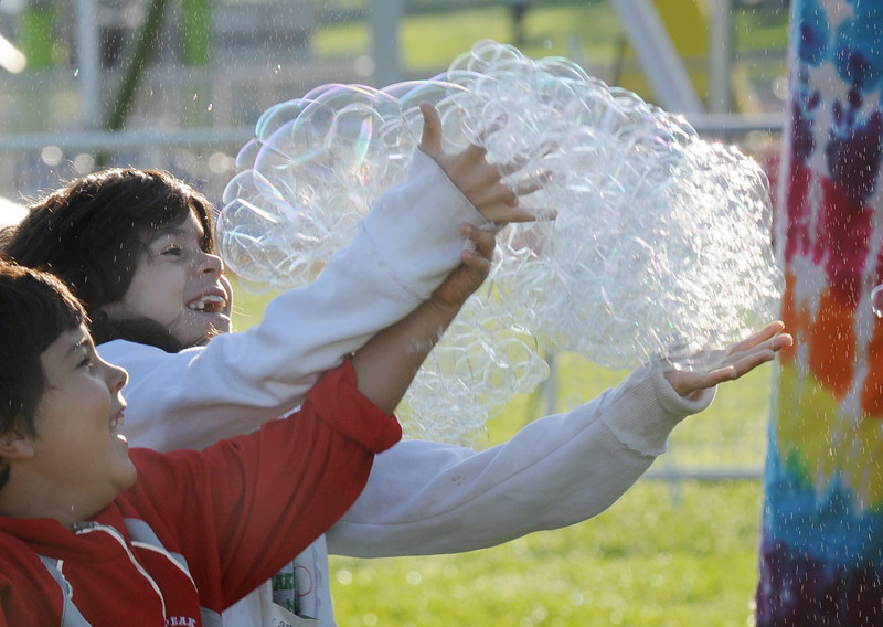 Austin Valdez, 7, left, and his sister Alena, 9, grab a group of bubbles during Broomfield Days at Midway Park on Saturday.<br /> <br /> Sept. 19, 2009<br /> Staff photo/David R. Jennings