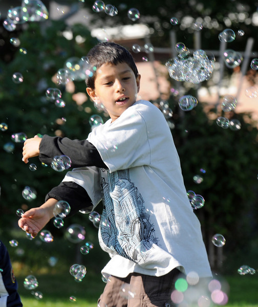 Sulaiman Birashk, 7, chases bubbles from the bubble machine during Broomfield Days at Midway Park on Saturday.<br /> <br /> Sept. 19, 2009<br /> Staff photo/David R. Jennings