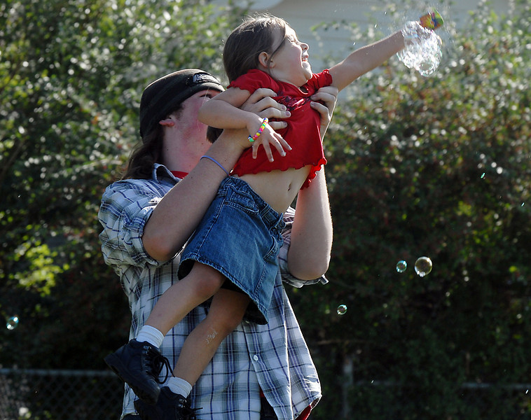 James Kenaley holds his niece Issa Trippett, 4, as they try to catch bubbles at Broomfield Days on Saturday.<br /> <br /> September 18, 2010<br /> staff photo/David R. Jennings