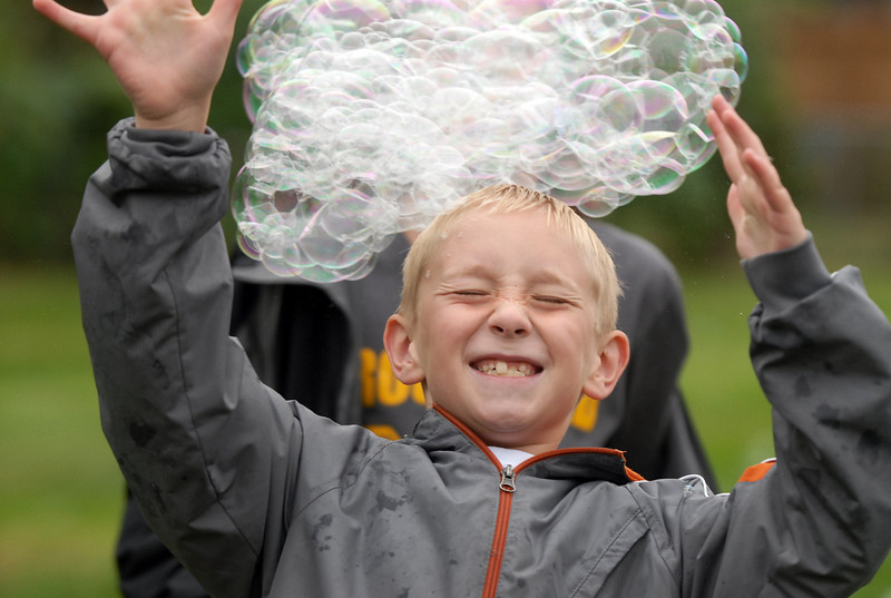 George Anast, 8, plays with a large cluster of bubbles from the bubble tower at Broomfield Days on Saturday.<br /> <br /> September 18, 2010<br /> staff photo/David R. Jennings