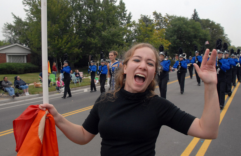 Maggie Admire with the Broomfield High flag team waves at the crowd while marching with the band during the parade at Broomfield Days on Saturday.<br /> <br /> September 18, 2010<br /> staff photo/David R. Jennings