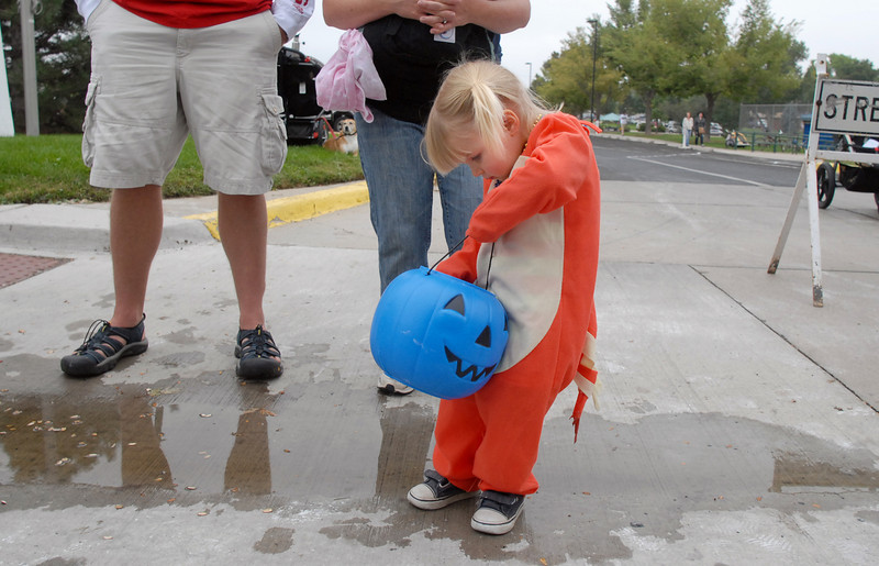 Adelina Pfitzer, 2, checks candy in a blue pumpkin pale while dressed in her Halloween costume during the parade at Broomfield Days on Saturday.<br /> <br /> September 18, 2010<br /> staff photo/David R. Jennings