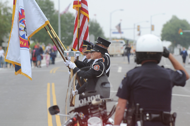The combined North Metro and Broomfield Police Honor Guard present the colors to start the parade as the Broomfield Police motorcycle officers salute  at Broomfield Days on Saturday.<br /> <br /> September 18, 2010<br /> staff photo/David R. Jennings