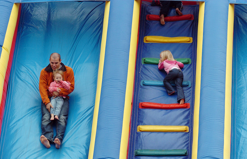 People slide down as others climb up the inflatable slide at Broomfield Days on Saturday.<br /> <br /> September 18, 2010<br /> staff photo/David R. Jennings