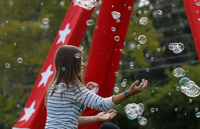 Arianna Bly, 13, chases after bubbles from the bubble machine during Broomfield Days at Midway Park on Saturday. September 17, 2011 staff photo/ David R. Jennings