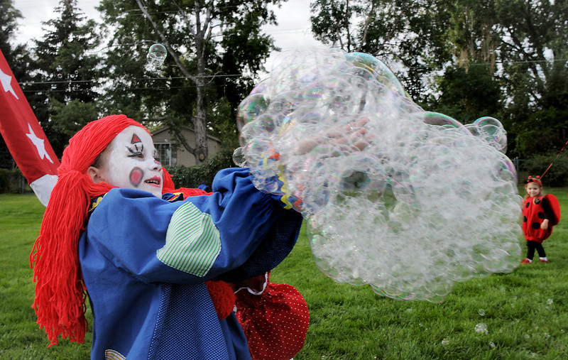 Alaina Harris, 7, dressed as a clown for the Optimist Clown Contest, catches bubbles during Broomfield Days at Midway park on Saturday.<br /> September 17, 2011<br /> staff photo/ David R. Jennings