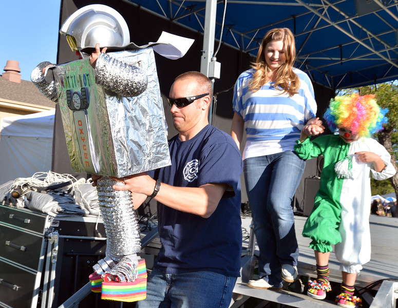 Clint Verseman carries his son Mattison, 4, dressed as a robot, off the stage for the Optimist Clown Contest during Broomfield Days at Midway Park.<br /> September 15, 2012<br /> staff photo/ David R. Jennings