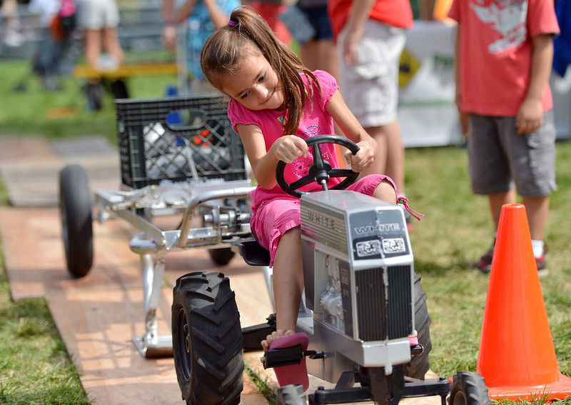 NIkki Sattig, 7, pedals hard moving 32 lbs over 26.4 feet in the Pedal Tractor Pull  during Broomfield Days at Midway Park.<br /> September 15, 2012<br /> staff photo/ David R. Jennings