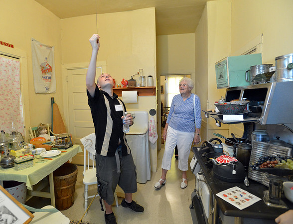 Tour guide Michael Sheinberg, 17, left, turns on the light to the kitchen  for Lois Jouett  during a tour of the Broomfield Depot Museum for the open house on Saturday.<br /> <br /> June23, 2012<br /> staff photo/ David R. Jennings