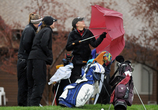 Callie Hodgkinson, right, Skyline, holds an umbrella to help shield Lauren Hamilton, Broomfield, and Kacey Fagler, Berthoud, from the  rain on the 12th during the tournament Thursday at Eagle Trace Golf Course.<br /> <br /> April 22, 2010<br /> Staff photo/David R. Jennings