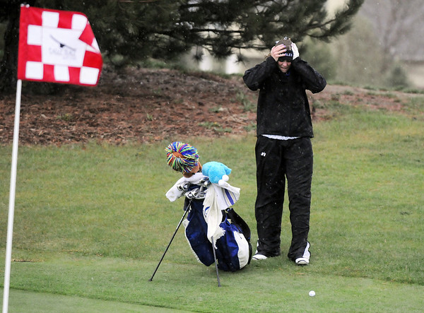 Broomfield's Lauren Hamilton tries to shield herself from the rain on the 11th during the tournament Thursday at Eagle Trace Golf Course.<br /> <br /> April 22, 2010<br /> Staff photo/David R. Jennings