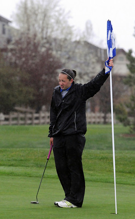 Broomfield's Taylor Dorans holds the flag in the rain on the 13th during Thursday's tournament at Eagle Trace Golf Course.<br /> <br /> April 22, 2010<br /> Staff photo/David R. Jennings