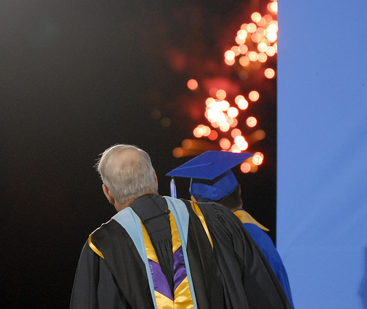 Darius Nazemi and Emerald Elementary principal Larry Leatherman, left, look around the back drop to watch fire works shooting off from Eagle Trace Golf Course before the turning of the tassels at Saturday's  Broomfield High graduation at Elizabeth Kennedy Stadium.<br /> May 22, 2010<br /> Staff photo/ David R. Jennings