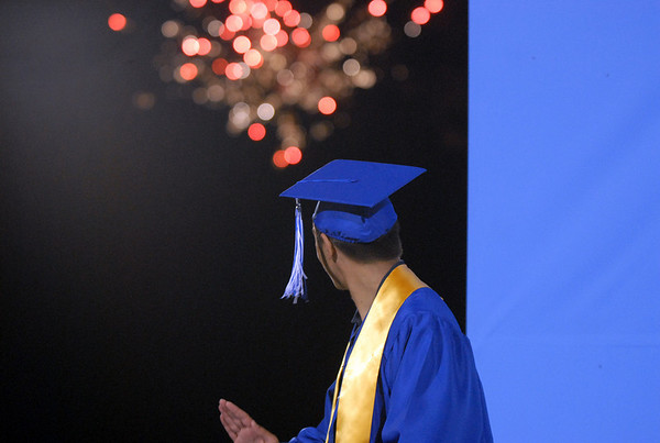 Darius Nazemi looks around the back drop to watch fire works shooting off from Eagle Trace before giving his speech for the turning the tassels at Saturday's  Broomfield High graduation at Elizabeth Kennedy Stadium.<br /> May 22, 2010<br /> Staff photo/ David R. Jennings
