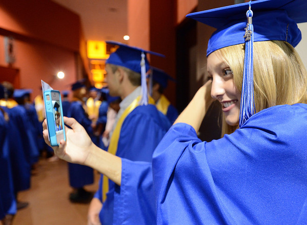 Kelli Marquardt uses a phone as a mirror to check her hair before Saturday's Broomfield High School Commencement at the 1stBank Center.<br /> <br /> May 19, 2012 <br /> staff photo/ David R. Jennings