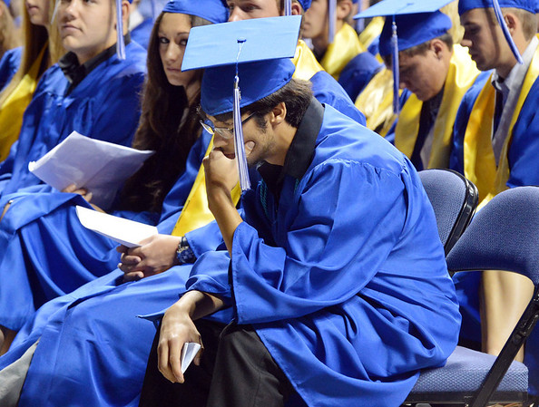 After giving his class member speech, Leon Miriles sits in contemplation remebering a classmate who died last year, Dylan Thomas, during Saturday's Broomfield High School Commencement at the 1stBank Center.<br /> <br /> May 19, 2012 <br /> staff photo/ David R. Jennings