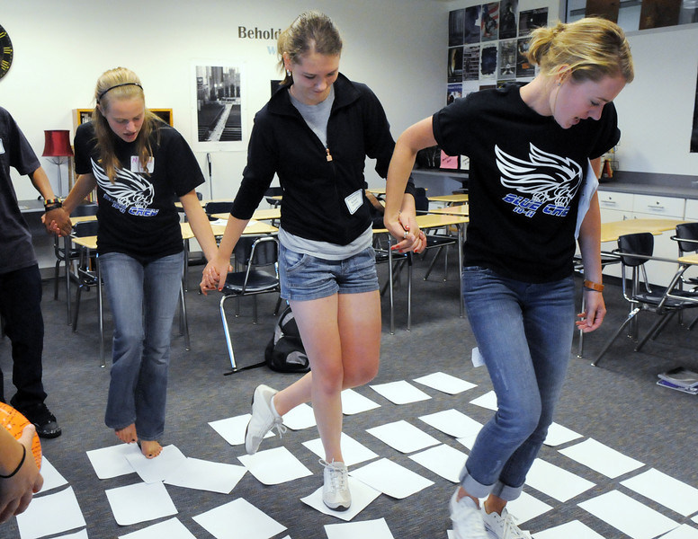 Broomfield High School Blue Crew leaders Kathryn Middle-Katzenmeyer, right, and Madison Goering, left, help freshman Rachel McCormick through a puzzle activity during Tuesday's freshman transition day.<br /> August 17, 2010<br /> staff photo/David R. Jennings