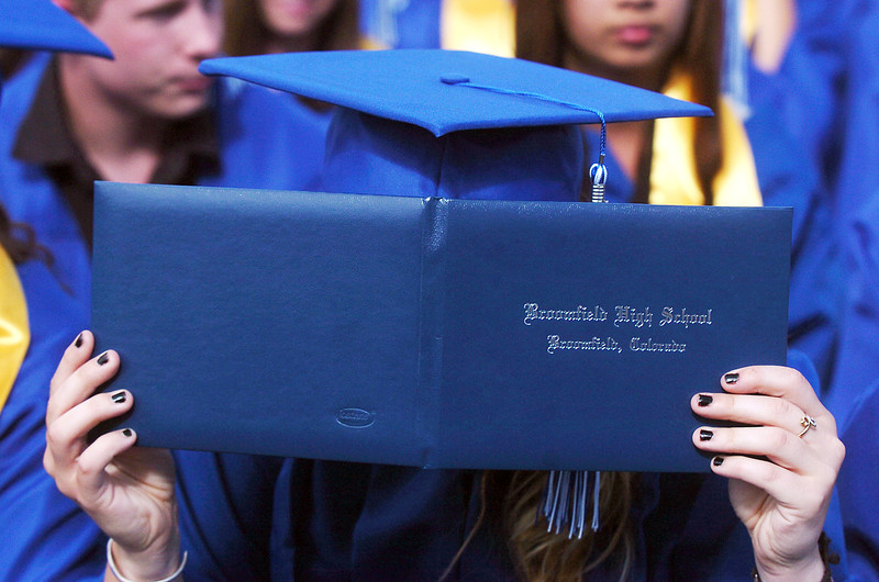 Jessica Eatmon hides behind her diploma during Saturday's Broomfield High School graduation ceremony at Elizabeth Kennedy Stadium.<br /> May 21, 2011<br /> staff photo/David R. Jennings