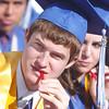 Scott Fiedler chews on a licorice stick during Saturday's Broomfield High School graduation ceremony at Elizabeth Kennedy Stadium.<br /> May 21, 2011<br /> staff photo/David R. Jennings