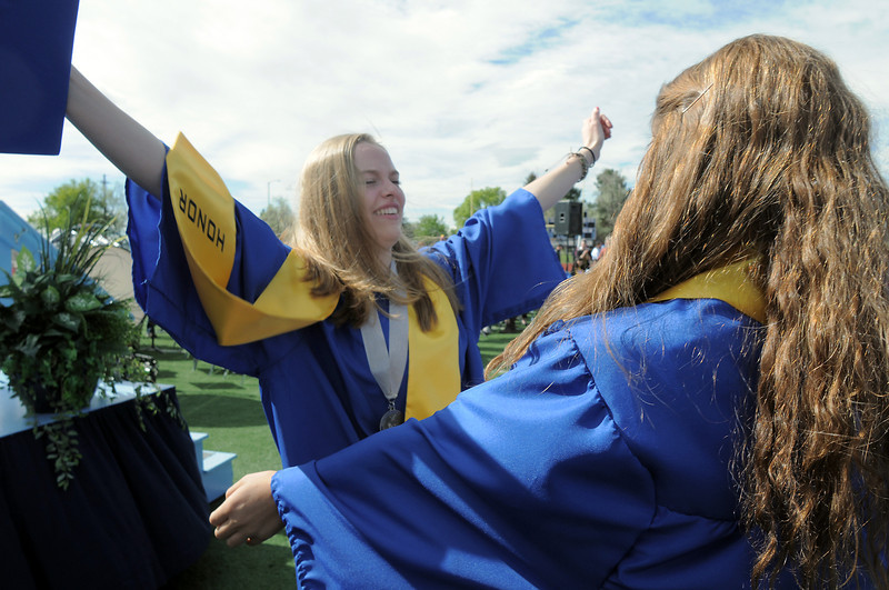Madison Goering, left, reaches to hug Kayla Baker afterSaturday's Broomfield High School graduation ceremony at Elizabeth Kennedy Stadium.<br /> May 21, 2011<br /> staff photo/David R. Jennings