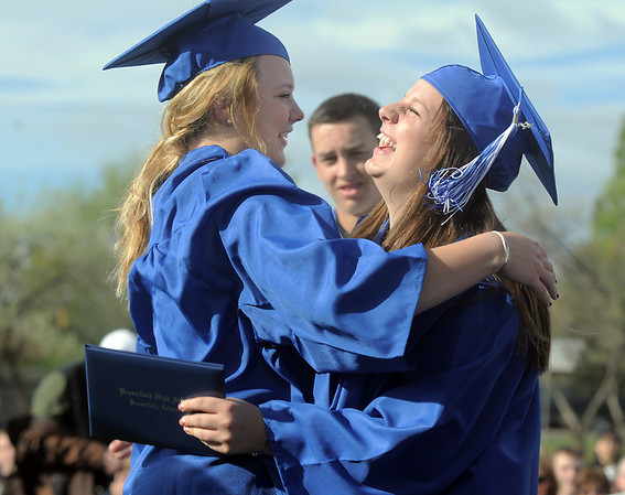 Jessica Eatmon, left, gives Abby Spencer a hug after receiving their diplomas during Saturday's Broomfield High School graduation ceremony at Elizabeth Kennedy Stadium.<br /> May 21, 2011<br /> staff photo/David R. Jennings