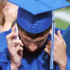 Tristan Voss talks to his work letting them know he's at his graduation during Saturday's Broomfield High School commencement  ceremony at Elizabeth Kennedy Stadium.<br /> May 21, 2011<br /> staff photo/David R. Jennings