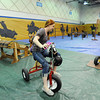 Taylor Lindquist, 14, center, rides a giant tricycle through the barrel racing course with Nickie Timson, 14, left, and Nic Moschetti, 14,  during the public tour of Broomfield High's JAM,  Just After Midnight , at the school on Saturday. <br /> <br /> April 28, 2012 <br /> staff photo/ David R. Jennings