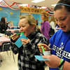 Ellie Keeler, 10, left, and Annemarie Abeyta, 11, eat yogurt in the country fair section during the public tour of Broomfield High's JAM,  Just After Midnight , at the school on Saturday. <br /> <br /> April 28, 2012 <br /> staff photo/ David R. Jennings