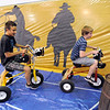 Ben Gibble, 16, left, races Nick Johnston, 16, in the barrel racing course riding giant tricycles during the public tour of Broomfield High's JAM,  Just After Midnight , at the school on Saturday. <br /> <br /> April 28, 2012 <br /> staff photo/ David R. Jennings