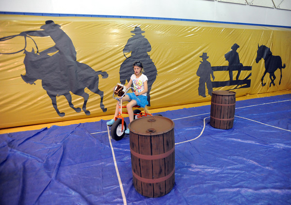 Courtney Wristen, 9, rides a giant tricycle through the barrel racing course during the public tour of Broomfield High's JAM,  Just After Midnight , at the school on Saturday. <br /> <br /> April 28, 2012 <br /> staff photo/ David R. Jennings