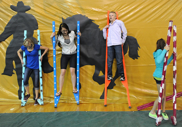 Emilee Schwartz, 12, left, Camille Laufasa-Duncan, 13, and Tyler Long, 13, try walking on stilts during the public tour of Broomfield High's JAM,  Just After Midnight , at the school on Saturday. <br /> <br /> April 28, 2012 <br /> staff photo/ David R. Jennings