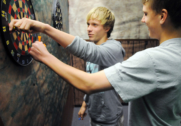 Thomas O'Brien, 14, left, and Blake Seitz, 14, pull darts out after throwing darts in the Irish Pub room during the Just After Midnight open house  at Broomfield High School on Saturday. <br /> April 24, 2010<br /> Staff photo/ David R. Jennings