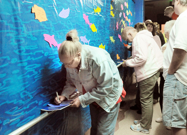 Diana Holder writes a note for her grandson Driss Collaso on the fish note wall during the Just After Midnight open house  at Broomfield High School on Saturday. <br /> <br /> April 24, 2010<br /> Staff photo/ David R. Jennings
